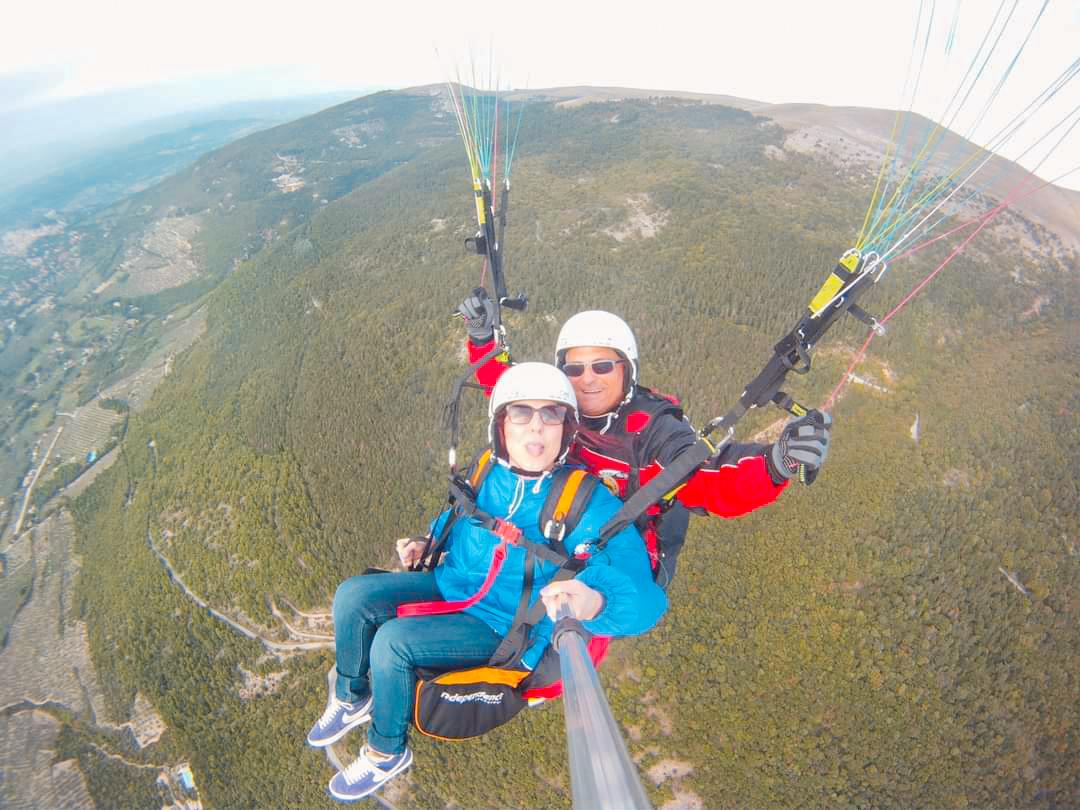 due persone sul parapendio e sullo sfondo il monte Subasio